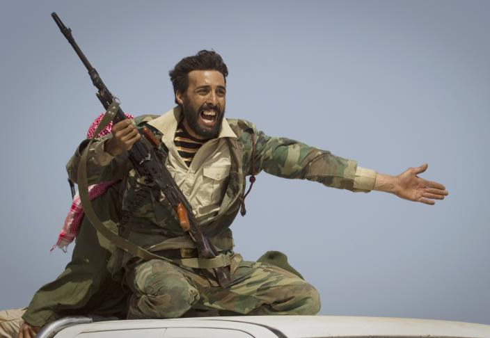 A Libyan rebel urges people to leave, as shelling from Gadhafi's forces started landing on the frontline outside of Bin Jawaad, 150 km east of Sirte, central Libya, Tuesday, March 29, 2011.