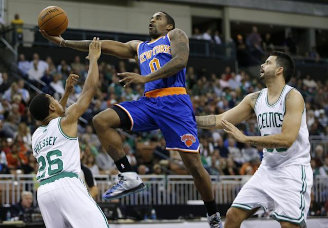 New York Knicks' Chris Smith (0) goes up to shoot against Boston Celtics' Phil Pressey (26) and Vitor Faverani (38) in the third quarter of an NBA preseason basketball game in Manchester, N.H., Saturday, Oct. 12, 2013. The Celtics won 111-81. (AP Photo/Michael Dwyer)