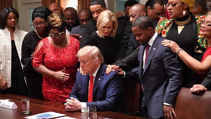 US President Donald Trump (C) stands in a prayer circle with African-American leaders