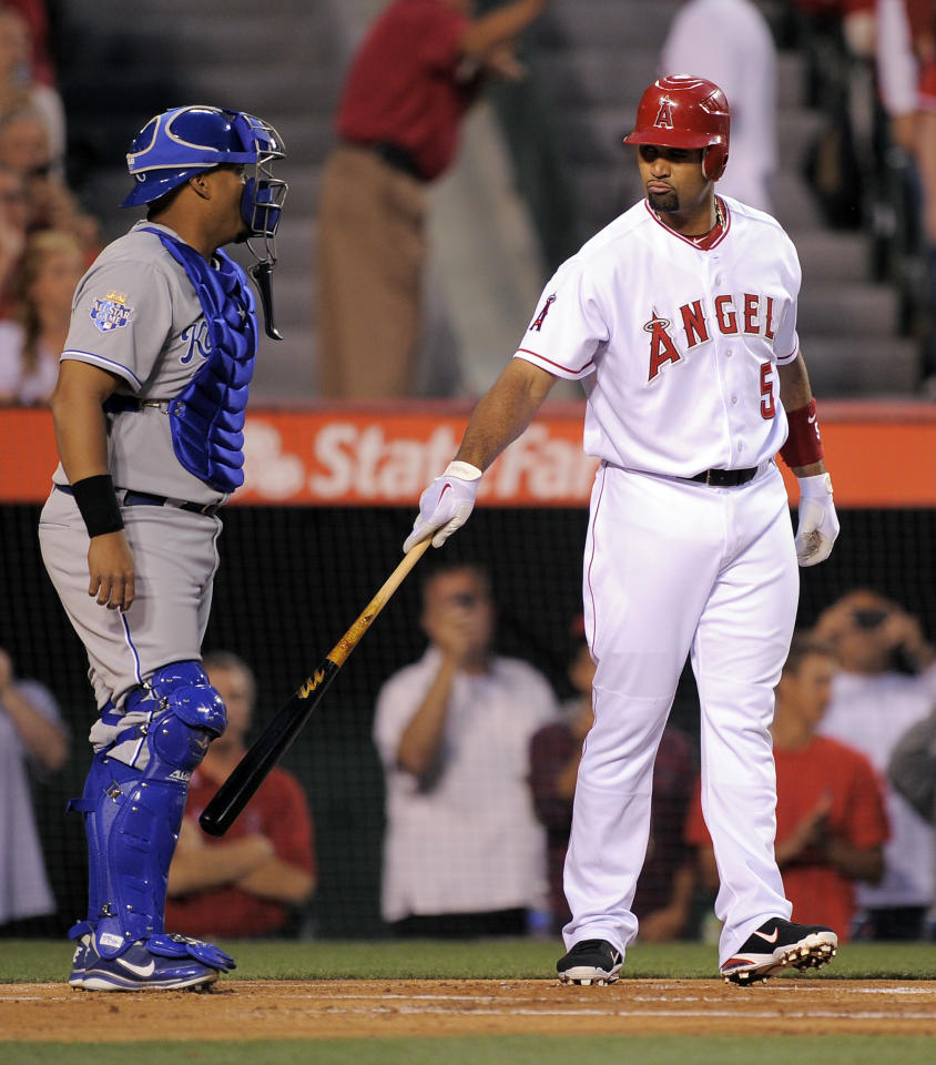 Los Angeles Angels' Albert Pujols, right, greets Kansas City Royals catcher Brayan Pena while coming up to bat during the first inning of a baseball game on Friday, April 6, 2012, in Anaheim, Calif. (AP Photo/Mark J. Terrill)