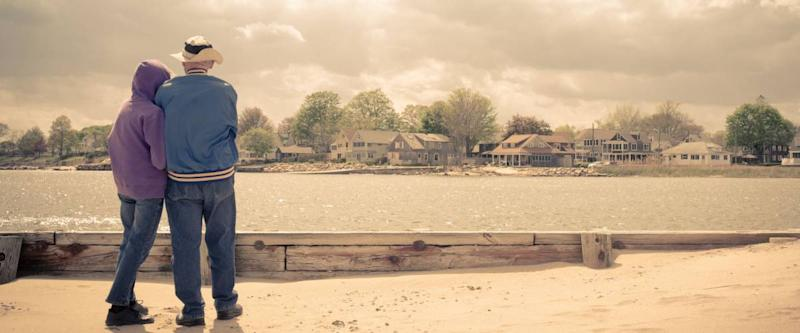 An older couple on the beach looking across the water at beautiful waterfront homes. Vintage effect applied.