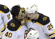 Boston Bruins defenseman Brandon Carlo (25) and goaltender Tuukka Rask (40) celebrate after they defeated the New Jersey Devils in a shootout in an NHL hockey game Thursday, Jan. 14, 2021, in Newark, N.J. (AP Photo/Bill Kostroun)