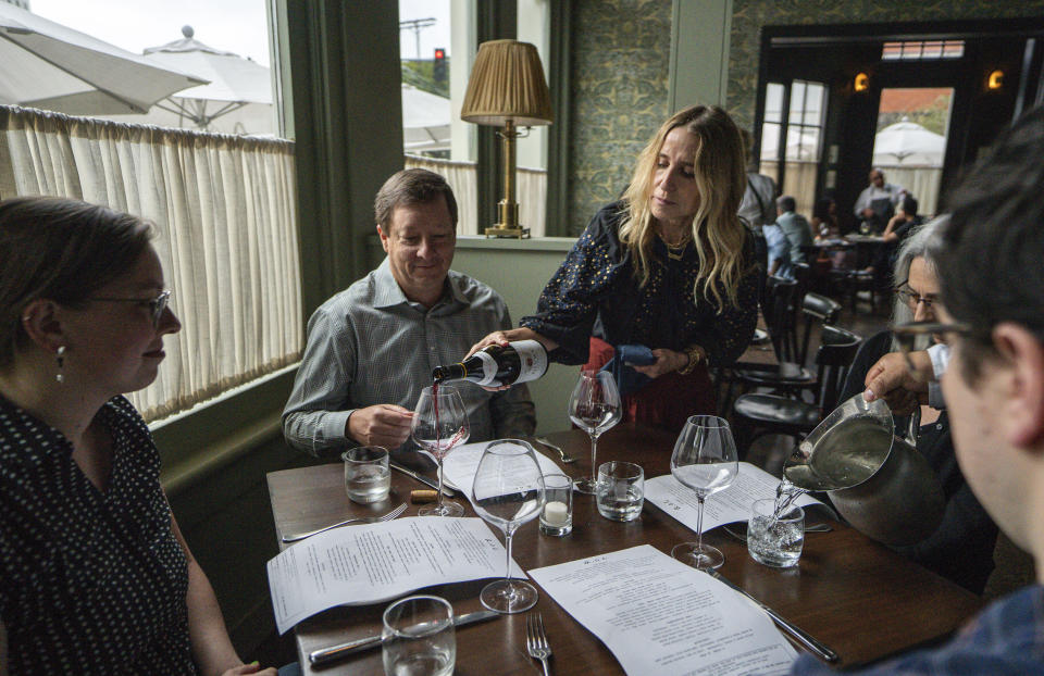 FILE - In this June 19, 2021, file photo, Caroline Styne, owner and wine director at The Lucques Group, serves wine to attorney Alec Nedelman, at the A.O.C. Brentwood restaurant in Los Angeles. Public health officials in Los Angeles County will begin requiring proof of COVID-19 vaccination for patrons and workers at indoor bars, wineries, breweries and nightclubs next month. The new initiative in the nation's most populous county begins Oct. 7, 2021 with proof of at least one vaccine dose required. (AP Photo/Damian Dovarganes, File)
