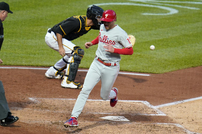 Philadelphia Phillies' Brad Miller, center, scores on a sacrifice fly by pitcher Aaron Nola off Pittsburgh Pirates starting pitcher JT Brubaker during the fifth inning of a baseball game in Pittsburgh, Saturday, July 31, 2021. Receiving the late relay throw is catcher Jacob Stallings. (AP Photo/Gene J. Puskar)