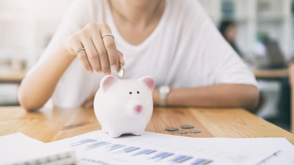 Woman sits at table with investment charts on pieces of paper, she's putting coins into a piggy bank.