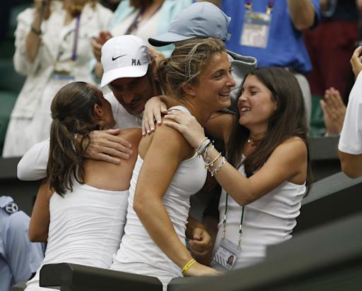 Sara Errani of Italy, second right, and Roberta Vinci of Italy, left, embrace family and friends in the players box after defeating Timea Babos of Hungary and Kristina Mladenovic of France in the women's doubles final at the All England Lawn Tennis Championships at Wimbledon, London, Saturday July 5, 2014. (AP Photo/Pavel Golovkin)