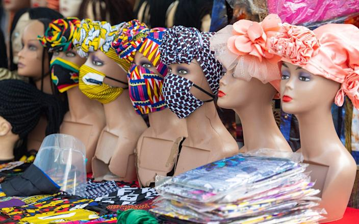 Protective face masks and plastic visors for sale at Ridley Road Market, in Dalston, London - Dominic Lipinski/PA