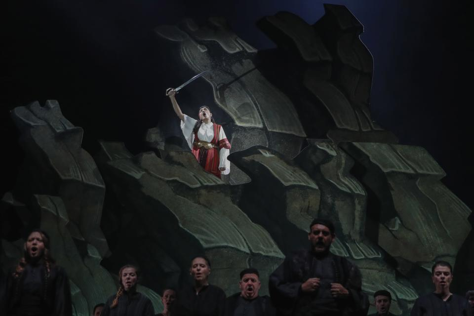 """Greek soprano Artemis Bogri holding a sword, sings during a rehearsal of """"Despo-Greek Dances"""" Opera and dance performance in Athens, Thursday, March 4, 2021. Dozens of museum exhibitions, theater productions, discussion panels and historical re-enactments were planned in Greece for this year to commemorate the bicentennial of the 1821-1832 Greek War of Independence. But due to the coronavirus pandemic, mezzo-soprano Artemis Bogri and her fellow singers stepped onstage in an empty theater to perform the Greek National Opera's new production of """"Despo,"""" one of the events marking 200 years since the war that resulted in Greece's independence from the Ottoman Empire and rebirth as a nation. (AP Photo/Thanassis Stavrakis)"""