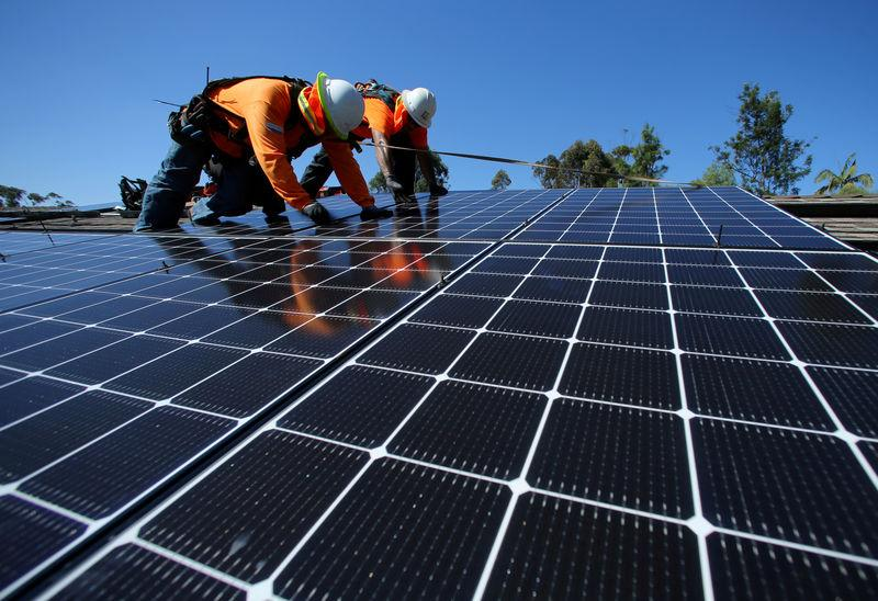 Solar installers from Baker Electric place solar panels on the roof of a residential home in Scripps Ranch, San Diego, California