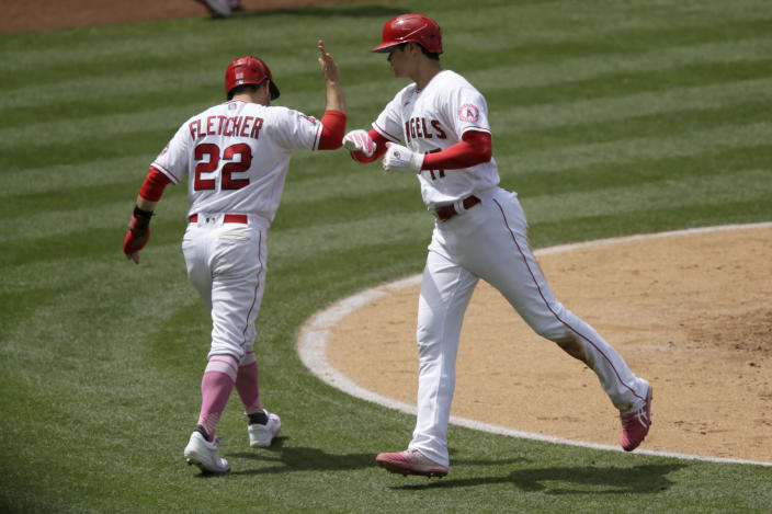 Los Angeles Angels' David Fletcher, left, greets designated hitter Shohei Ohtani after they scores on a ground-rule double by Jared Walsh during the third inning of a baseball game against the Los Angeles Dodgers in Anaheim, Calif., Sunday, May 9, 2021. (AP Photo/Alex Gallardo)