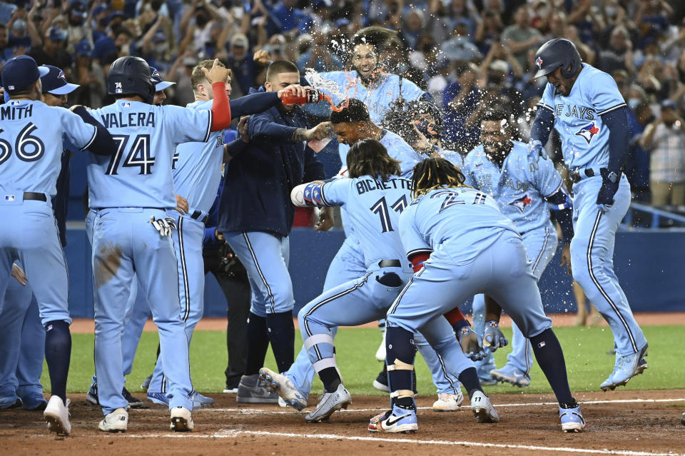 Toronto Blue Jays' Marcus Semien, center, celebrates with teammates after hitting a three-run walkoff home run against the Oakland Athletics in the ninth inning of a baseball game in Toronto, Friday, Sept. 3, 2021. (Jon Blacker/The Canadian Press via AP)