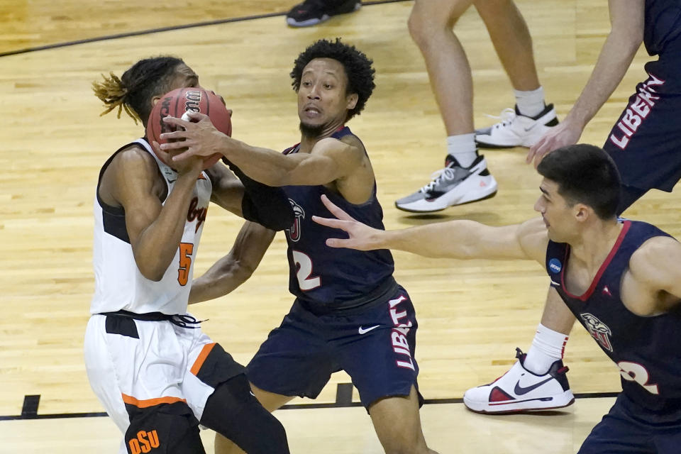 Liberty's Darius McGhee (2) fouls Oklahoma State guard Rondel Walker (5) as Blake Preston also defends in a first-round NCAA tournament game. (AP Photo/Charles Rex Arbogast)