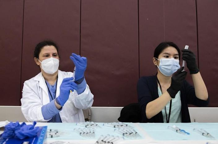 Pharmacists Nabilah Seblini and Julie Nguyen prepare syringes with the COVID-19 vaccine made by Johnson & Johnson at a high school in Detroit.