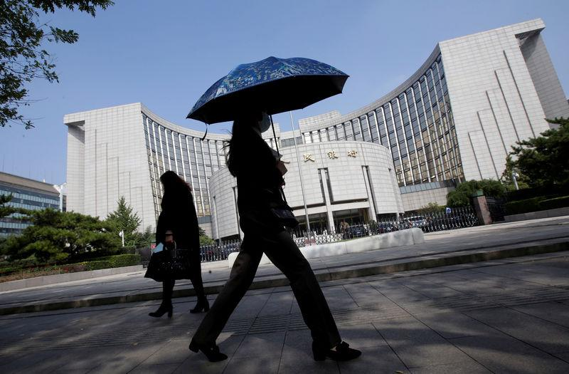 FILE PHOTO: People walk past the headquarters of the People's Bank of China (PBOC), the central bank, in Beijing, China September 28, 2018. REUTERS/Jason Lee/File Photo