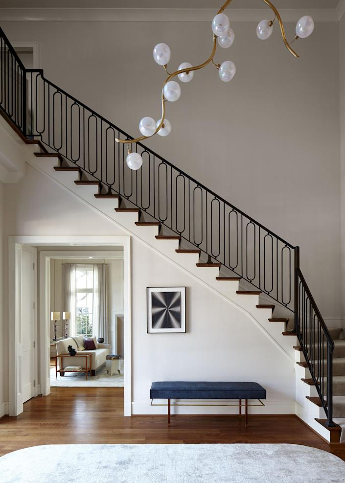 """The home's central staircase, which features new iron railing chosen by Liss, features a Harvey Probber bench in mahogany and brass, set under a Mark Gortjahn drawing, purchased at <a href=""""https://pettitartpartners.com"""" rel=""""nofollow noopener"""" target=""""_blank"""" data-ylk=""""slk:Pettit Art Partners"""" class=""""link rapid-noclick-resp"""">Pettit Art Partners</a>. The striking ceiling light is a custom piece by Jeff Zimmerman from <a href=""""https://www.r-and-company.com"""" rel=""""nofollow noopener"""" target=""""_blank"""" data-ylk=""""slk:R & Company"""" class=""""link rapid-noclick-resp"""">R & Company</a>."""