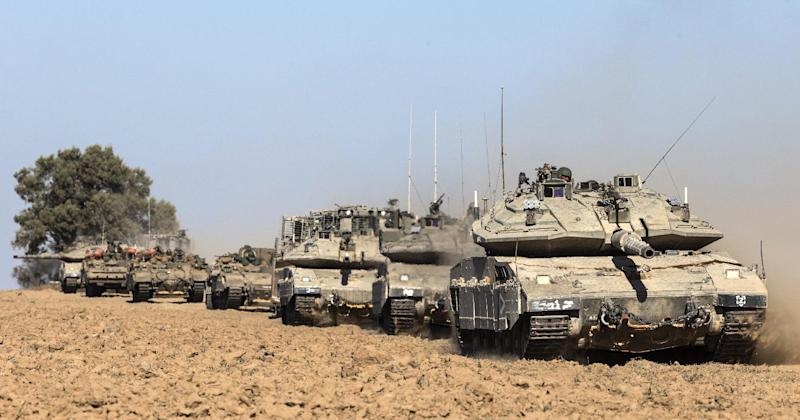 Israeli Merkava tanks, a D9 bulldozer and armoured personnel carriers roll near Israel's border with the Gaza Strip on July 17, 2014