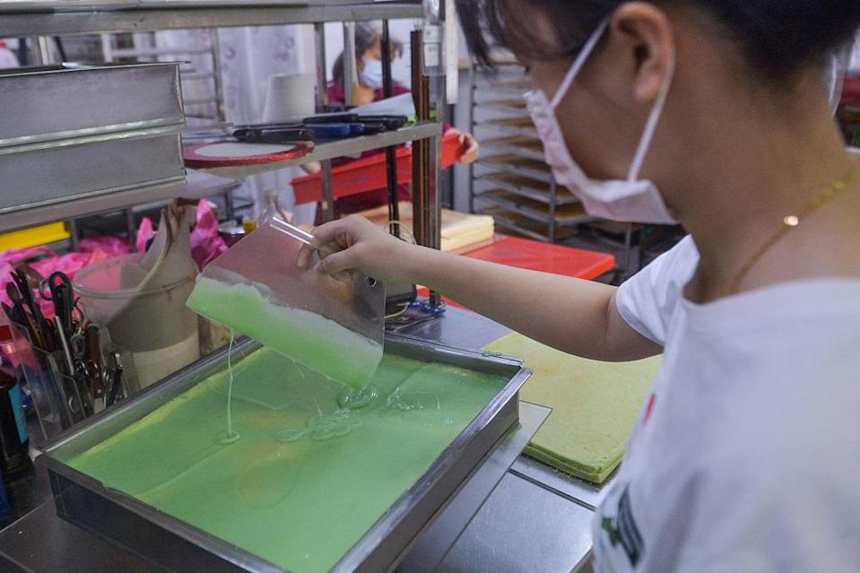 A  Meru Golden Bake worker prepares their signature Pandan Layer cake to be distributed to several bakery shops owned by the other family members in Klang June 23, 2021.