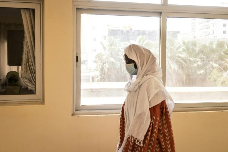 A woman waits to get vaccinated with the Oxford/AstraZeneca vaccine against Covid-19 at Ngor Clinic in Dakar