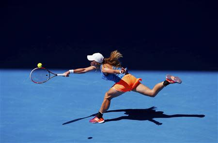 Johanna Larsson of Sweden hits a return to Victoria Azarenka of Belarus during their women's singles match at the Australian Open 2014 tennis tournament in Melbourne January 14, 2014. REUTERS/Petar Kujundzic