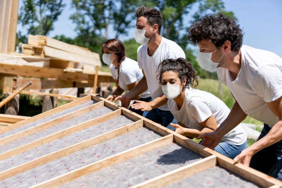 Group of Latin American volunteers building a house fo charity while wearing a facemask during the COVID-19 pandemic