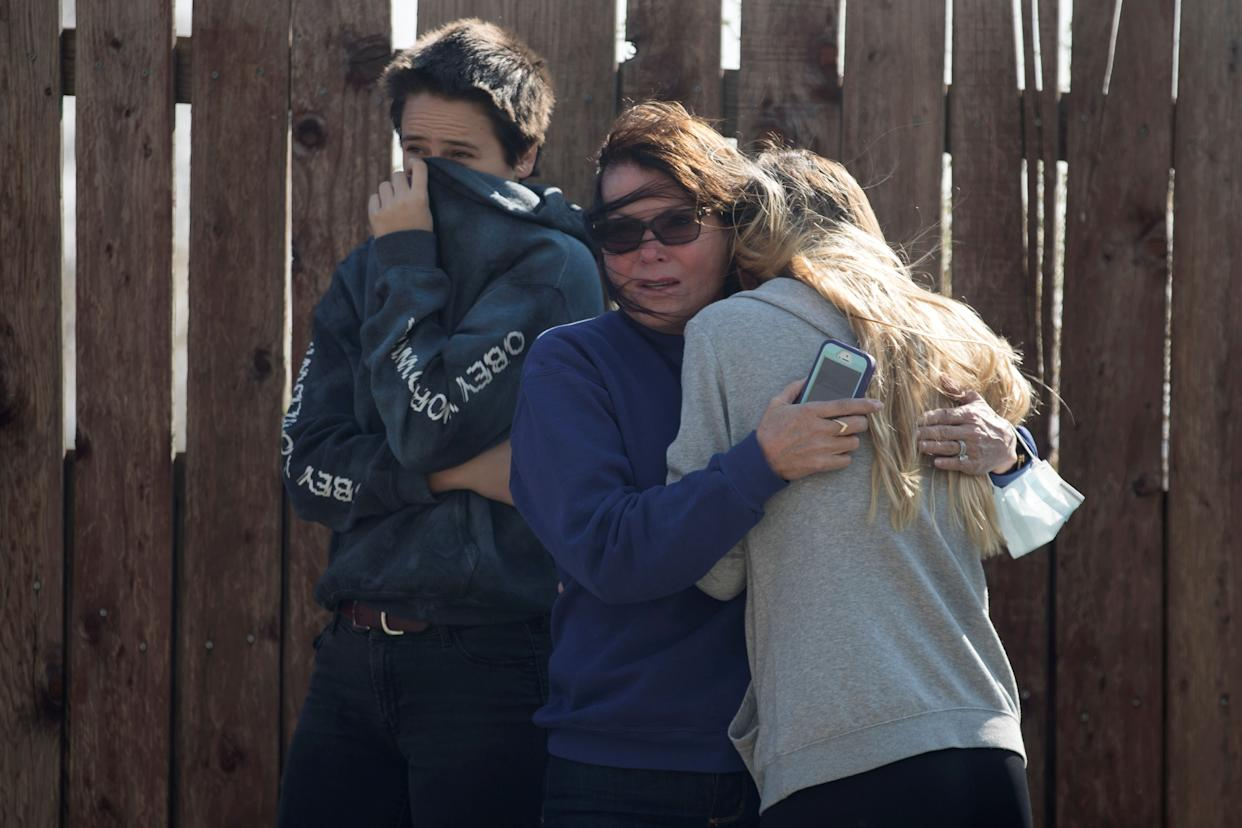 Local residents react as numerous homes burn on a hillside in Ventura County.