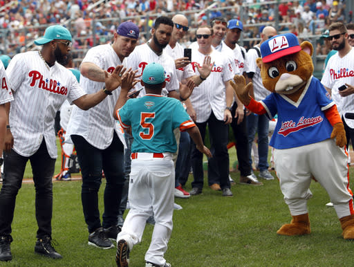 Panama's Adam Villarreal (5) high fives Philadelphia Phillies Carlos Santana and Asdrubal Cabrera during player introductions of their game against Japan in an International pool play baseball game at the Little League World Series tournament in South Williamsport, Pa., Sunday, Aug. 19, 2018. Japan won the game 4-2. (AP Photo/Tom E. Puskar)