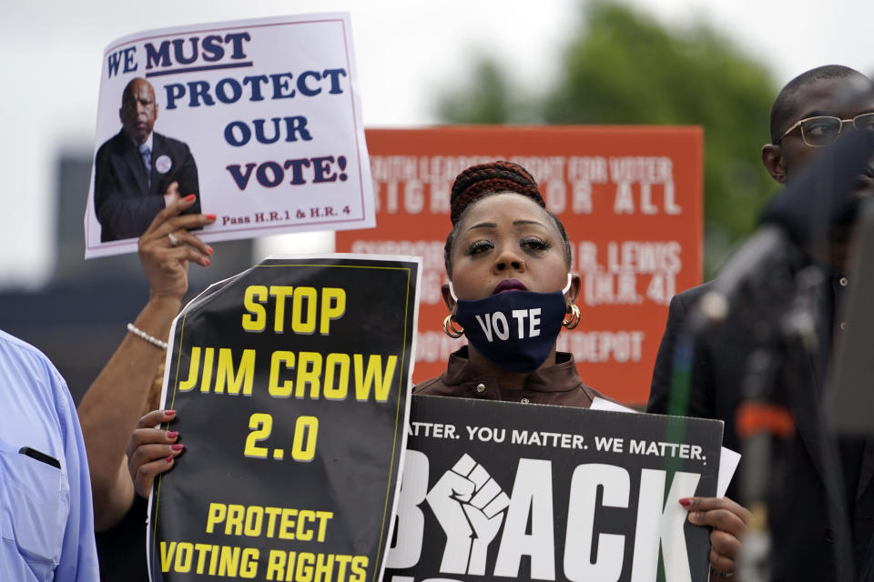 A person holds up signs during a voting rights rally at Liberty Plaza near the Georgia State Capitol on Tuesday, June 8, 2021, in Atlanta. (AP Photo/Brynn Anderson)