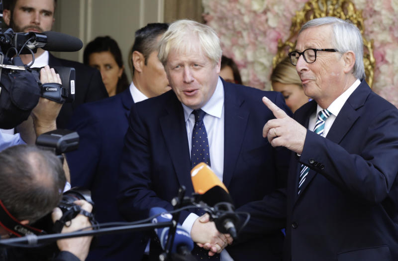 European Commission President Jean-Claude Juncker, right, speaks with the media as he shakes hands with British Prime Minister Boris Johnson prior to a meeting at a restaurant in Luxembourg, Monday, Sept. 16, 2019. British Prime Minister Boris Johnson was holding his first meeting with European Commission President Jean-Claude Juncker on Monday in search of a longshot Brexit deal. (AP Photo/Olivier Matthys)