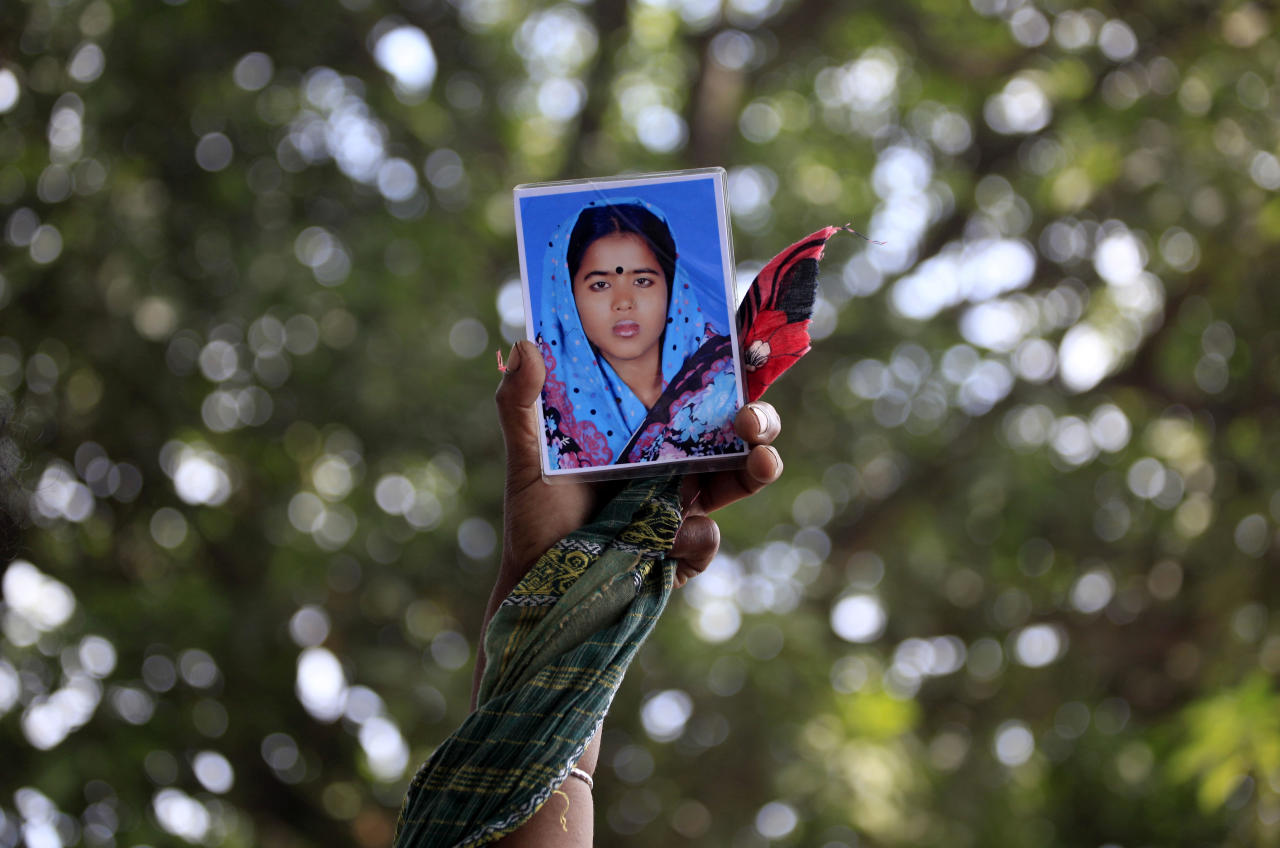 A woman holds up a portrait of her missing relative, Thursday, May 2, 2013, in Savar, near Dhaka, Bangladesh. Rescuers found more bodies in the concrete debris of a collapsed garment factory building Thursday and authorities said it may take another five days to clear the rubble. In addition to the 430 confirmed dead, police report another 149 people are still missing in what has become the worst disaster for Bangladesh's $20 billion-a-year garment industry that supplies global retailers. (AP Photo/Ismail Ferdous)