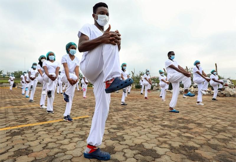 Dozens of masked male and female health workers stand in formation as they stretch in sync.