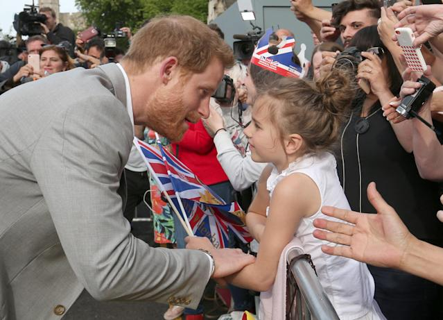 Prince Harry talks with a young girl during a walkabout in Windsor ahead of his wedding to Meghan Markle. Photo: Ben Birchall/pool via Reuters)