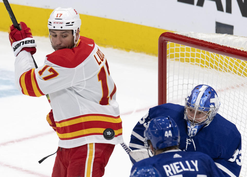Toronto Maple Leafs goaltender David Rittich (33) and Calgary Flames' Milan Lucic (17) keep a close eye on the puck as it bounces during the third period of an NHL hockey game Tuesday, April 13, 2021 in Toronto. (Frank Gunn/Canadian Press via AP)