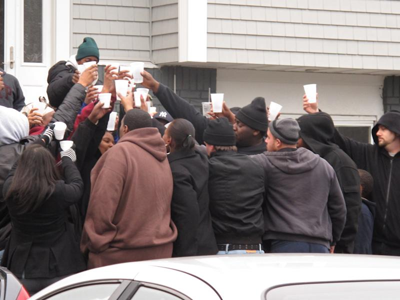 Friends and relatives of Kansas City Chiefs linebacker Jovan Belcher drink a toast outside the player's home on Saturday, Dec. 1, 2012, in West Babylon, N.Y. The Long Island native shot and killed his girlfriend then killed himself on Saturday in Kansas City.(AP Photo/Frank Eltman)