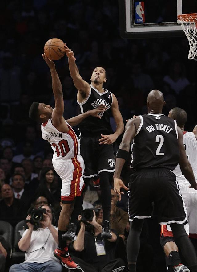 Brooklyn Nets' Shaun Livingston (14) blocks a shot by Miami Heat's Norris Cole (30) during the first half of an NBA basketball game on Friday, Jan. 10, 2014, in New York. The Nets won the game 104-95. (AP Photo/Frank Franklin II)
