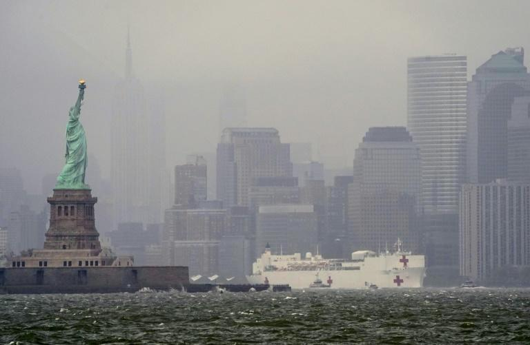 The hospital ship USNS Comfort passes the Statue of Liberty as its departs New York City on April 30, 2020 (AFP Photo/TIMOTHY A. CLARY)