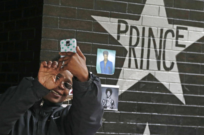 FILE - In this April 22, 2016, file photo, a fan takes a selfie by the Prince star and memorial at First Avenue in Minneapolis where he often performed. The one-year anniversary of the pop super star's death from an overdose will be marked April 21. (AP Photo/Jim Mone, File)