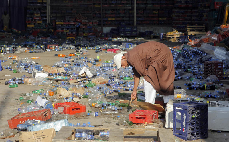 An Egyptian checks destroyed soft drinks bottles a a Christian owned factory at Dahshour village, about 40 kilometers (25 miles) south of Cairo, Thursday, Aug. 2, 2012, a day after a sectarian violence erupted in the village following the death of a Muslim man, prompting most the local Christians to flee, church and security officials said. (AP Photo/Amr Nabil)