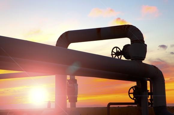 A twist of pipelines with a bright sun shining behind them.