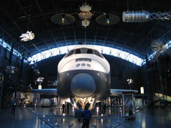 Space shuttle and other spacecraft in museum setting.