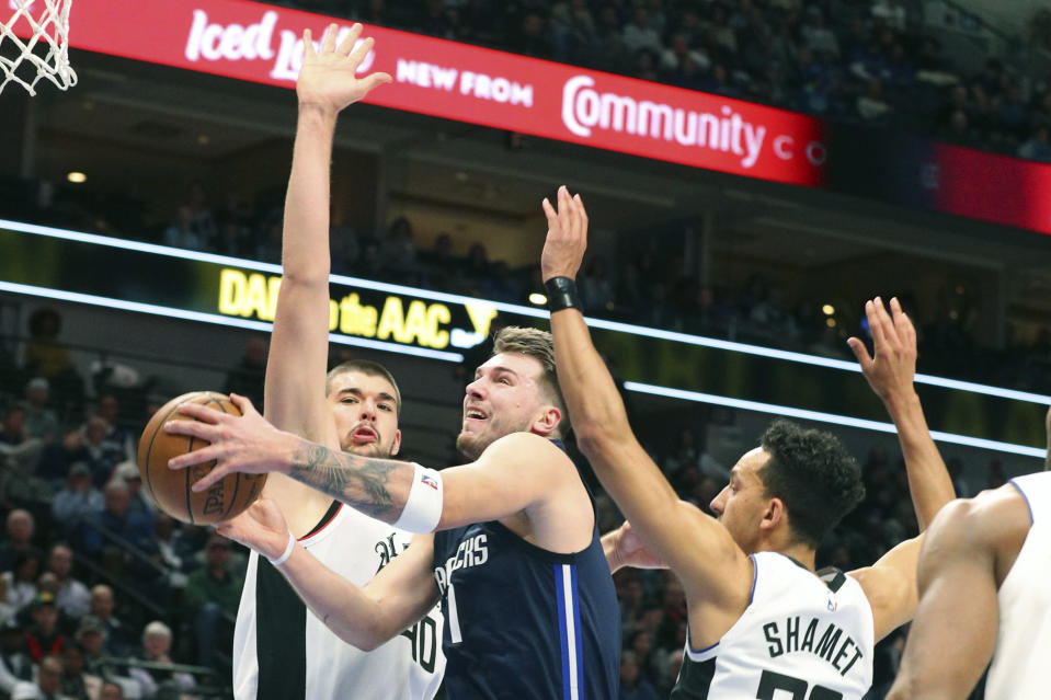 Dallas Mavericks forward Luka Doncic (77) goes up for a shot against Los Angeles Clippers center Ivica Zubac (40) and guard Landry Shamet (20) during the first half of an NBA basketball game Tuesday, Jan. 21, 2020 in Dallas. (AP Photo/Richard W. Rodriguez)