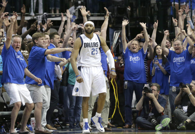 Fans cheer as Dallas Mavericks guard Vince Carter stands in the corner after he made the game-winning 3-point basket at the buzzer in the fourth quarter against the San Antonia Spurs in Game 3 in the first round of the NBA basketball playoffs in Dallas, Saturday, April 26, 2014. The Mavericks won 109-108. (AP Photo/LM Otero)