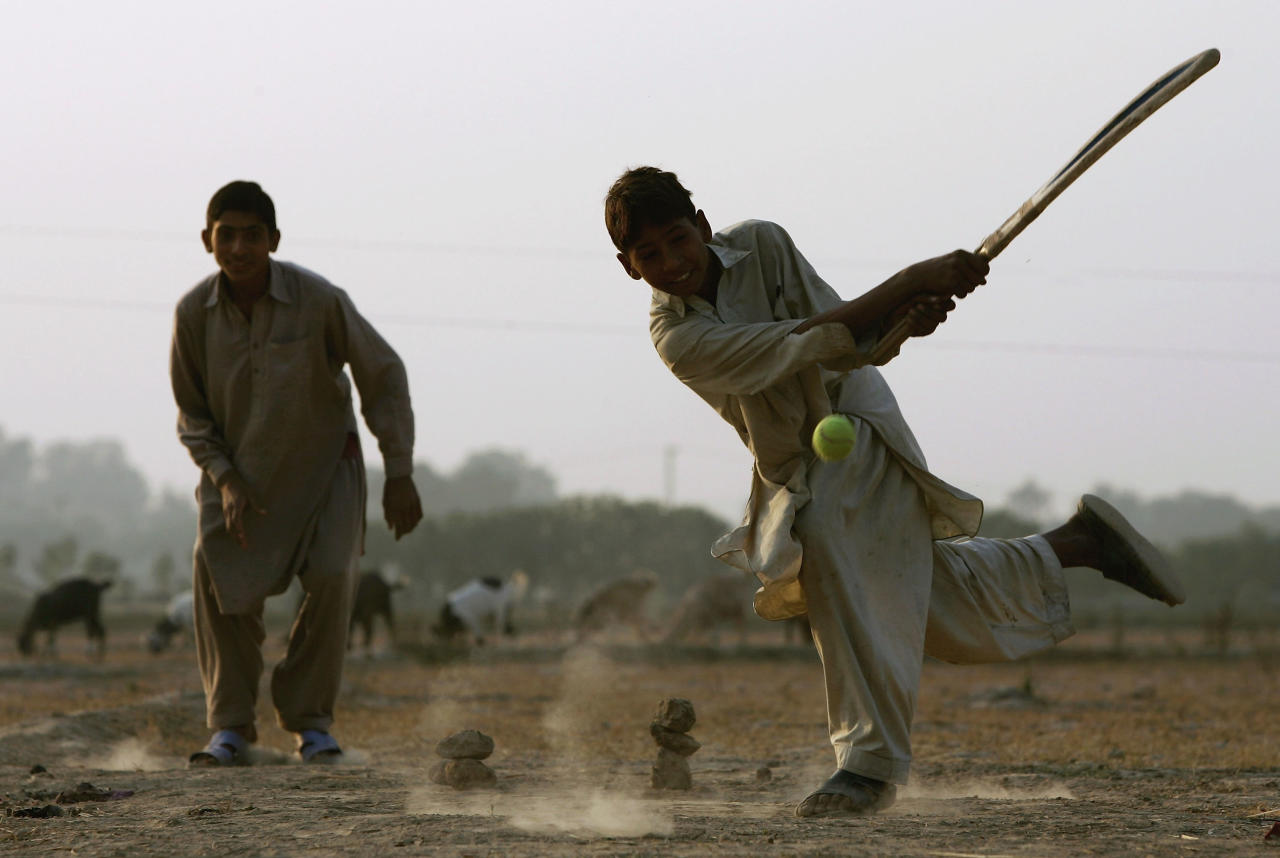 LAHORE, PAKISTAN - DECEMBER 06:  Local children enjoy a game of cricket in a field near the border of Pakistan and India during the England winter tour on December 6, 2005 in Wagah, Pakistan.  (Photo by Paul Gilham/Getty Images)