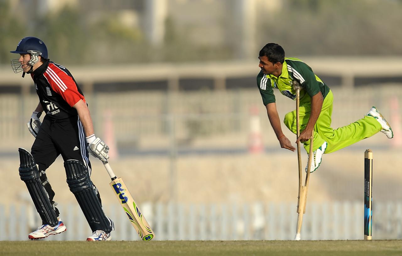 Pakistan disabled cricketer Farhan Saeed (R) delivers the ball as England disabled cricketer Gordon Laidlaw (L) look on during the T20 match between England Disaballity team and Pakistan Disaballity team at the ICC Global Cricket Academy (ICC GCA) in Dubai Sports City on February 11, 2012. Pakistan beat England in the first-ever Twenty20 match between the physically challenged cricket teams by 14 runs. AFP PHOTO/ LAKRUWAN WANNIARACHCHI (Photo credit should read LAKRUWAN WANNIARACHCHI/AFP/Getty Images)