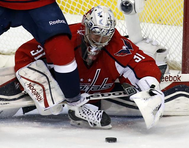 Washington Capitals goalie Philipp Grubauer (31), from Germany, reaches around a teammate's skate for the puck in the overtime period of an NHL hockey game against the Buffalo Sabres, Sunday, Jan. 12, 2014, in Washington. The Sabres won 2-1 in a shootout. (AP Photo/Alex Brandon)