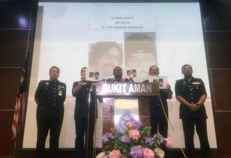 Malaysia's Inspector General of Police Mohamad Fuzi Harun shows media mugshots of a suspect involved in the murder of Fadi Albatsh, during a news conference in Kuala Lumpur