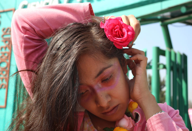 Activist Diana Ceballos places a rose in her hair as she prepares to take part in a procession for felled women like her 14-year old cousin, in Ecatepec, a suburb of Mexico City, Saturday, Nov. 23, 2019. Ceballos' cousin was raped and stabbed to death by an ex-boyfriend of the teenager's mother. He confessed via text message to the mother immediately after the 2014 murder. Even so, it took three years to clinch a jail sentence against the perpetrator. (AP Photo/Alicia Fernandez)