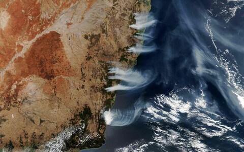 This NASA Earth Observatory handout from 4 December shows fires burning near the coast of New South Wales, near Canberra and areas north to the border with Queensland, Australia - Credit: Lauren Dauhpin/AFP