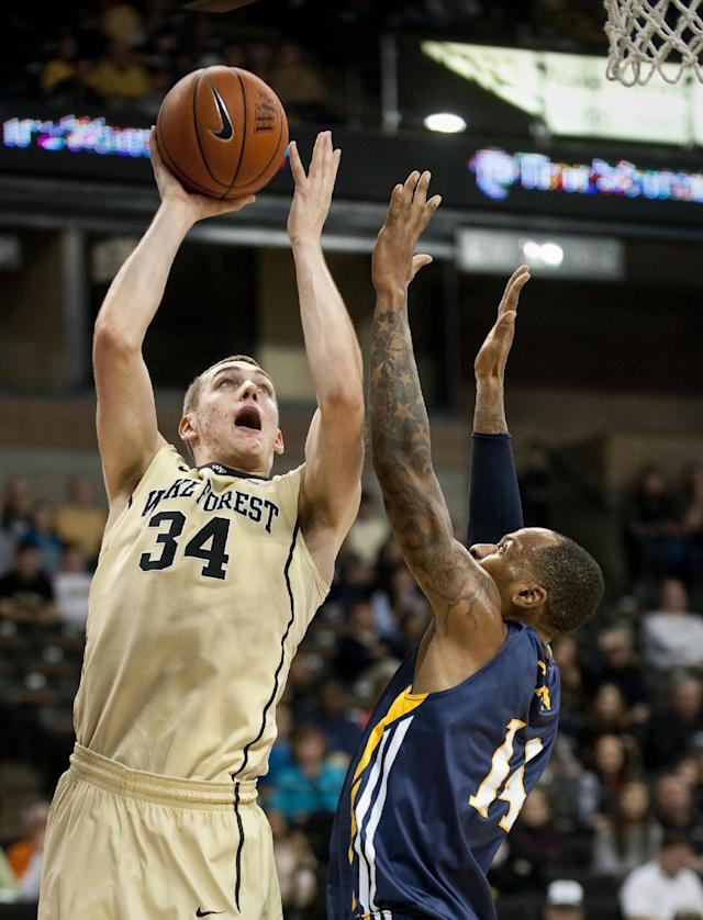 Wake Forest's Tyler Cavanaugh, left, goes up for a shot as UNC Greensboro' Kyle Cain defends during their NCAA college basketball game in Winston-Salem, N.C., Saturday, Dec. 21, 2013. (AP Photo/Winston-Salem Journal, Lauren Carroll)