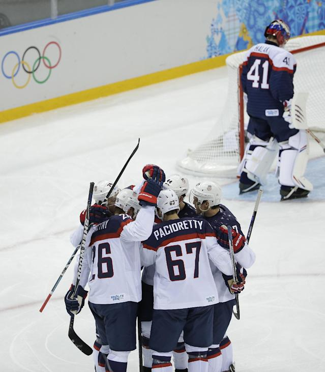 Team USA celebrates Paul Stastny's goal as Slovakia goaltender Jaroslav Halak skates in front of the net during the 2014 Winter Olympics men's ice hockey game at Shayba Arena, Thursday, Feb. 13, 2014, in Sochi, Russia. (AP Photo/Matt Slocum)