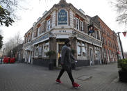 A man walks past the Duke of Sussex pub with a sign depicting the image of Britain's Prince Harry and his wife Meghan, near Waterloo station, London, Tuesday March 9, 2021. Prince Harry and Meghan's explosive TV interview has divided people around the world, rocking an institution that is struggling to modernize with claims of racism and callousness toward a woman struggling with suicidal thoughts. (AP Photo/Frank Augstein)